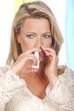 妇女应用鼻孔喷射 库存图片