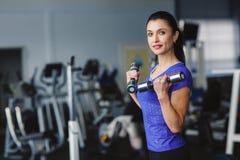 妇女应付在健身房的哑铃 免版税库存照片