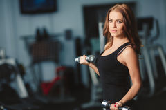 妇女应付在健身房的哑铃 免版税图库摄影
