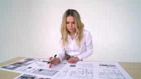 妇女建筑师在工作在她的办公室,研究新的项目;手图画,计算机图画 股票录像