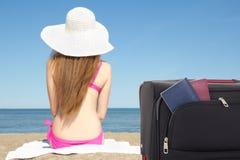 妇女开会和手提箱有护照的在海滩 免版税库存图片