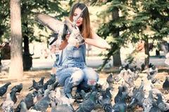 妇女开会和饲料鸽子种子 免版税图库摄影