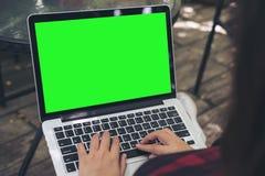 妇女开会的大模型图象,使用和键入在有空白的绿色屏幕的膝上型计算机在大腿在室外 库存照片