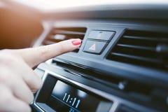 妇女开在汽车的应急灯 库存图片