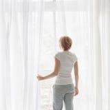 妇女开窗口帷幕 免版税库存照片