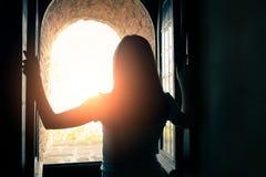 妇女开窗口并且享受风景 免版税库存照片