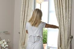 妇女开窗口 免版税库存照片
