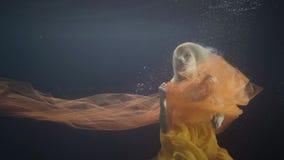 妇女式样游泳喜欢在黑暗的背景的美人鱼水下的水池 股票视频