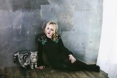 妇女式样美丽和时兴与在背景的一只猫 库存图片