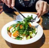 妇女强加了芝麻菜、三文鱼、鸡蛋、蕃茄和黄瓜沙拉在芥末-蜂蜜调味汁 免版税库存图片