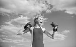 妇女强的拳击手套培养手蓝天背景 女孩拳击手套女性权利的标志奋斗和 免版税库存照片