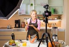 妇女录音录影在她的家庭厨房里,创造录影博克的内容 免版税库存图片