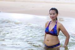 妇女形状巨大与比基尼泳装在海滩放松 库存图片