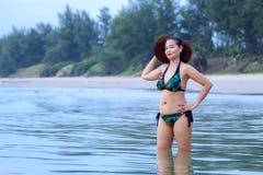 妇女形状性感的比基尼泳装和帽子在海滩 免版税库存照片