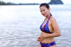 妇女形状美好与比基尼泳装在海滩放松 免版税库存照片