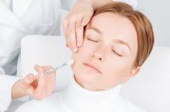 妇女得到在面颊的补白射入 防皱治疗和更新 对妇女的面孔的脸皮举的射入 免版税图库摄影