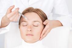 妇女得到射入 防皱治疗和更新 对妇女的面孔的脸皮举的射入 图库摄影