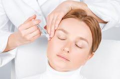 妇女得到射入 防皱治疗和更新 对妇女的面孔的脸皮举的射入 库存图片