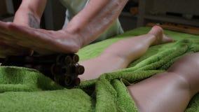 妇女得到放松在温泉沙龙的按摩 关闭按摩有竹疗法路辗的治疗师手女性腿 股票视频