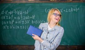 妇女微笑的老师举行书摊前面黑板 对学院概念的推荐 请求信件 免版税图库摄影