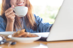 妇女微笑饮料咖啡和用途计算机 免版税库存照片