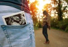妇女怀孕等待在森林里 免版税库存照片
