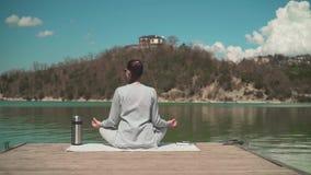 妇女思考得在阳光下,当坐湖的一个木码头,放松本质上时 r 股票录像