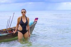 妇女性感的标志黑色比基尼泳装和小船在海滩 库存照片