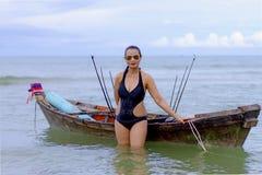 妇女性感的黑比基尼泳装和小船在海滩 免版税库存照片