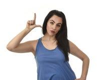 妇女恼怒的翻倒和哀伤的做的L签字与她手指代表更加宽松 库存照片