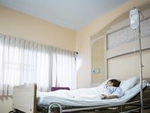 妇女患者在医院病床上 库存照片