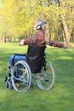 妇女愉快在有胳膊传播的一个轮椅 库存图片