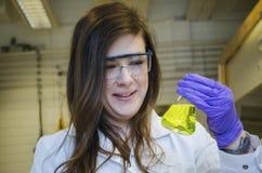 妇女愉快的科学家藏品和支付由一种黄色化工解答决定的注意关闭在化学实验室 库存照片