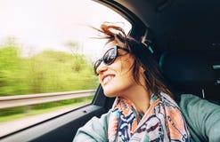 妇女感到自由并且从开窗口汽车看  库存照片