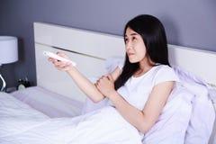 妇女感觉寒冷和手按在床上的遥远的空调器 免版税库存图片