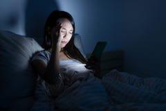 妇女感觉眼睛痛苦和使用手机在晚上 免版税图库摄影