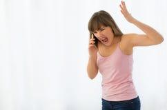 妇女愤怒谈话在电话 免版税库存照片