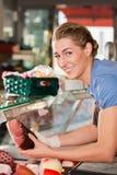 妇女或女性屠户用未加工的火腿在肉店 免版税库存图片