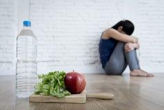 妇女或少年女孩在家坐地面单独担心的遭受的营养饮食失调 免版税库存照片