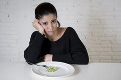 妇女或青少年与吃盘用可笑小的莴苣的叉子作为她的疯狂的饮食的食物标志 免版税库存照片