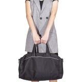 妇女手举行旅行袋子,在白色背景的黑颜色, 免版税库存照片