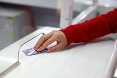 妇女手交通卡片到票入口火车站的插入物票 免版税图库摄影