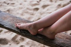 妇女手和腿在一块木头关闭户外 免版税库存照片