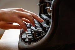妇女手在一台老葡萄酒被尘土覆盖的打字机键入 库存图片