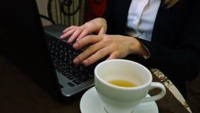 妇女手在有一杯的一个膝上型计算机键盘打印文本绿茶 股票视频