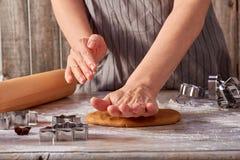 妇女手在桌卷起姜饼面团 免版税库存图片