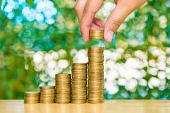 妇女手在步投入了硬币硬币堆和金币金钱 免版税库存照片