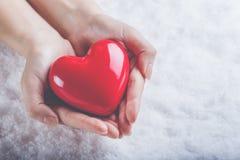 妇女手在雪背景中拿着美好的光滑的红色心脏 爱和圣华伦泰概念 库存图片