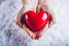 妇女手在雪背景中拿着美好的光滑的红色心脏 爱和圣华伦泰概念 免版税库存图片
