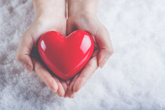 妇女手在雪背景中拿着美好的光滑的红色心脏 爱和圣华伦泰概念 免版税库存照片